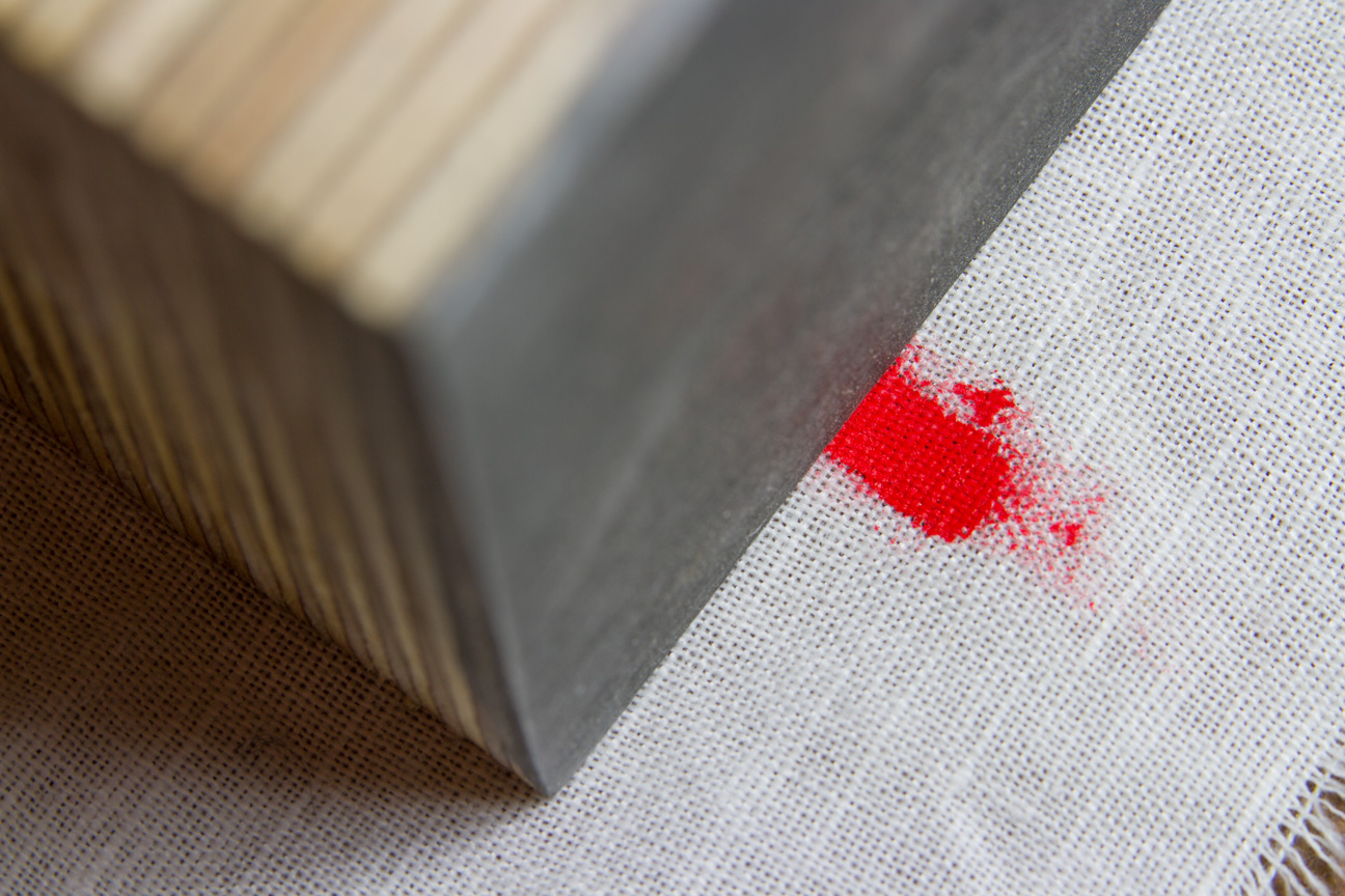 a piece of plywood on fabric with red color as example for a new abstract technology stock photo