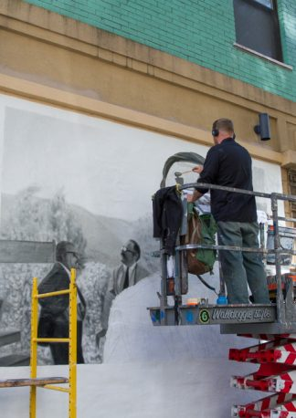 street artist painting a black and white artwork
