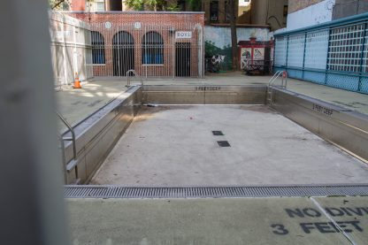 empty swimming pool with a red, yellow and green ball inside